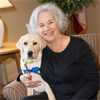 Carolyn Hrach smiling with yellow service dog