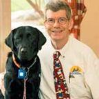 Dennis Sproule smiling with black lab