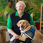 Judge Ed Kinkeade smiling with yellow service dog