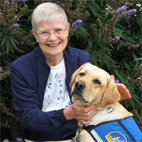 Jill Leverton smiling with yellow service dog