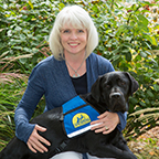Brenda Kennedy smiling with black service dog in lap