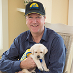 Jack Peirce smiling with small yellow lab puppy with cape