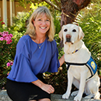 Paige Mazzoni, Canine Companions CEO sitting with service dogs