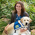 Sarah Birman with yellow service dog on her lap