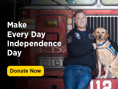 man leaning against firetruck with Canine Companions service dog sitting by his side