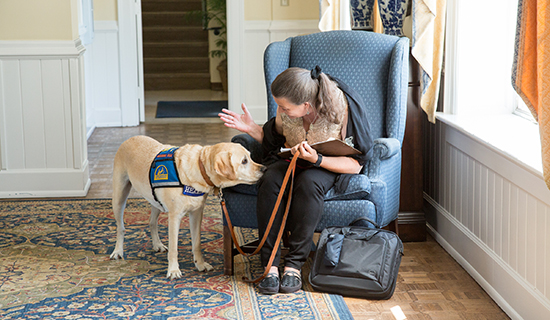 Woman sitting in chair with her Canine Companions Hearing Dog by her side