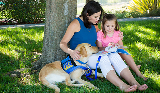 Young girl and mother lean against tree while reading with assistance dog