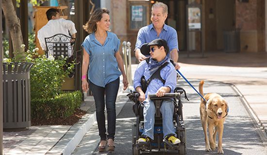 Man in wheelchair with family and assistance dog
