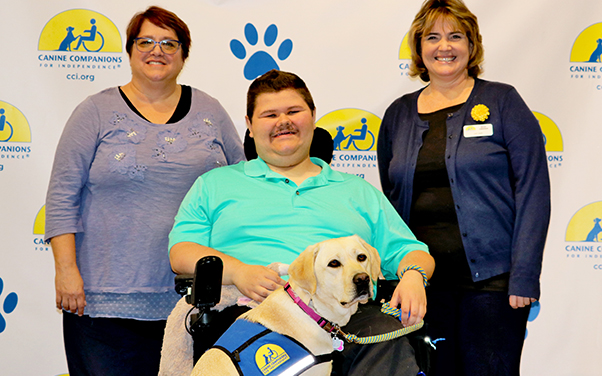 Canine companions yellow service dog with person sitting in wheelchair and two people standing behind him
