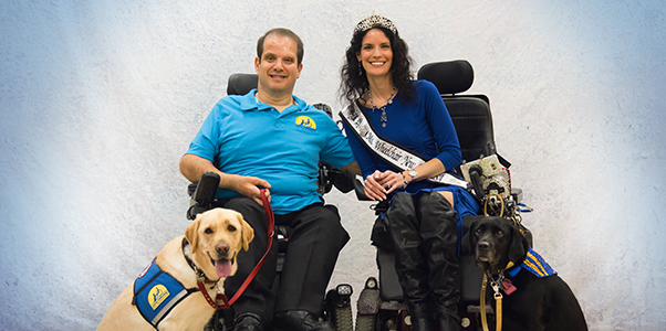 Woman wearing crown with a Miss wheelchair sash and crown next to man in wheelchair wearing blue Canine Companions shirt, both have a black and yellow Canine Companions dog sitting in front of them