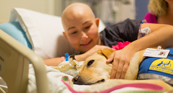 Teenaged girl smiles while cuddling facility dog in hospital bed