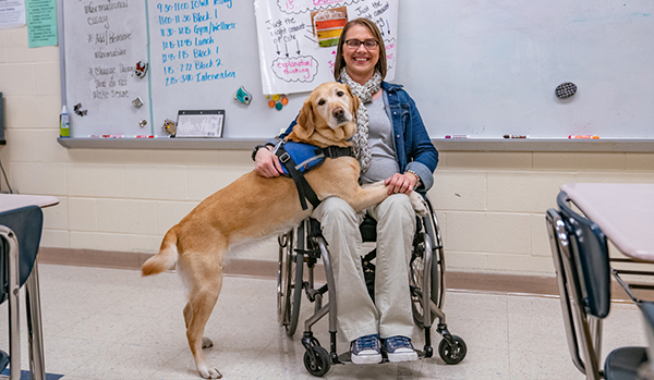 woman sitting in wheelchair with yellow Canine Companions service dog accross her lap