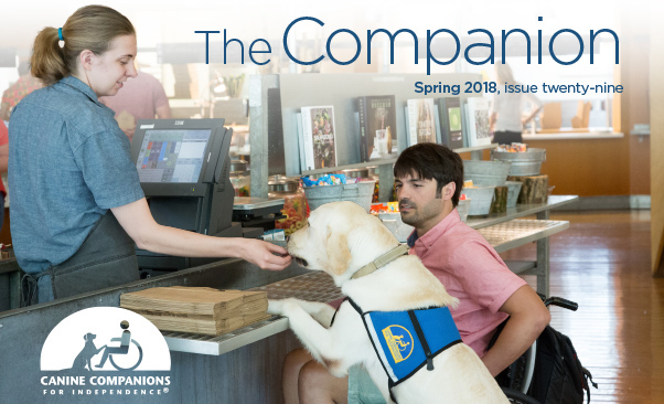 The Companion cover for Spring 2018, man in wheelchair with service dog accompanying him at register pictured