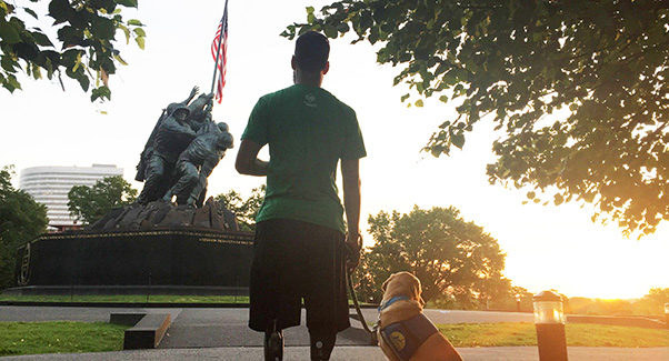 Veteran with yellow service dog look on at statue replicating famous the famous Iwo Jima war photo