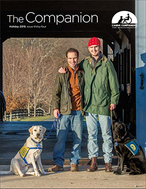 2019 Holiday Companion cover with two men standing next to each other holding the leashes to two Canine Companions dogs