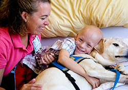 Facility dog lays with smiling young boy in hospital while handler looks on