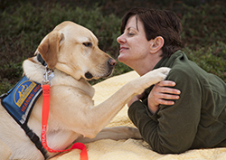 Graduate and her yellow hearing dog lay on a blanket in the grass