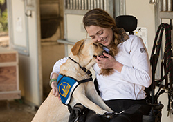 Woman sitting in wheelchair hugging a yellow Canine Companions Service Dog