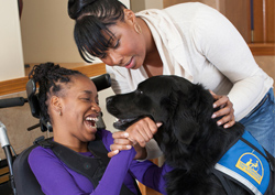 child and woman with black service dog