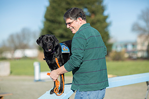 man training a Canine Companions dog in park