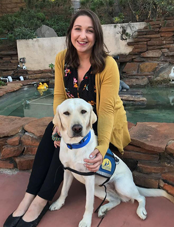 woman sitting next to Canine COmpanions service dog