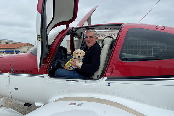 a yellow Canine Companions puppy sits with a volunteer pilot in the cockpit of his plane