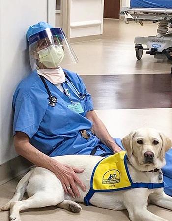 volunteer puppy raiser wearing hospital scrubs sitting next to Canine COmpanions puppy