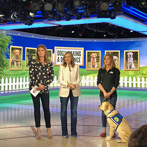 Meredith, Jenna and Canine companions instructor standing on stage with yellow dog wearing Canine Companions service dog vest