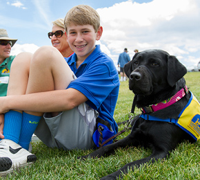 Boy smiling with black Canine Companions service dog