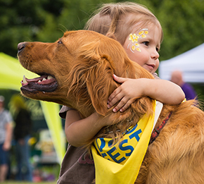 Young girl hugging golden retriever wearing a Canine Companions DogFest bandanna