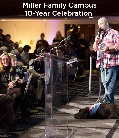stand-up comedian with black assistnace dog at his feet