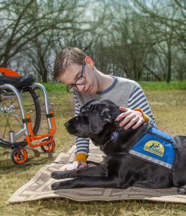 boy sitting on blanket with wheelchair in background and black Canine Companions service dog.