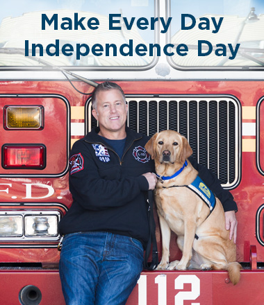 man leaning against firetruck with Canine Companions service dog by his side