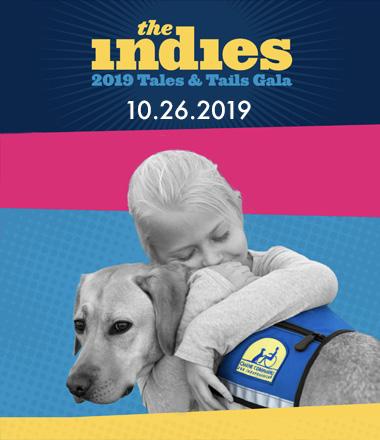 girl hugging a Canine Companions service dog