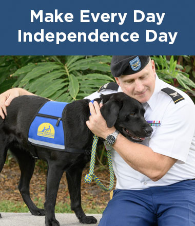 man wearing military attire hugging a Canine Companions service dog