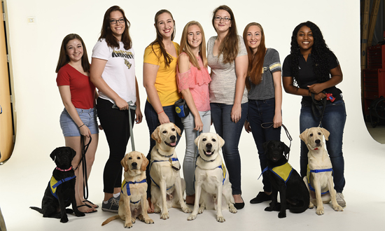 Group of Collegiate Puppy Raisers and the Canine Companions puppies they are raising