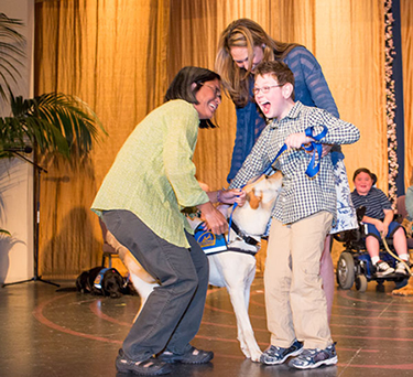 young boy receiving his assistance dog