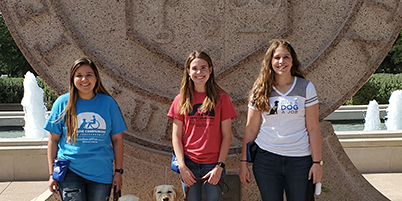 Three girls stand on Texas Tech campus