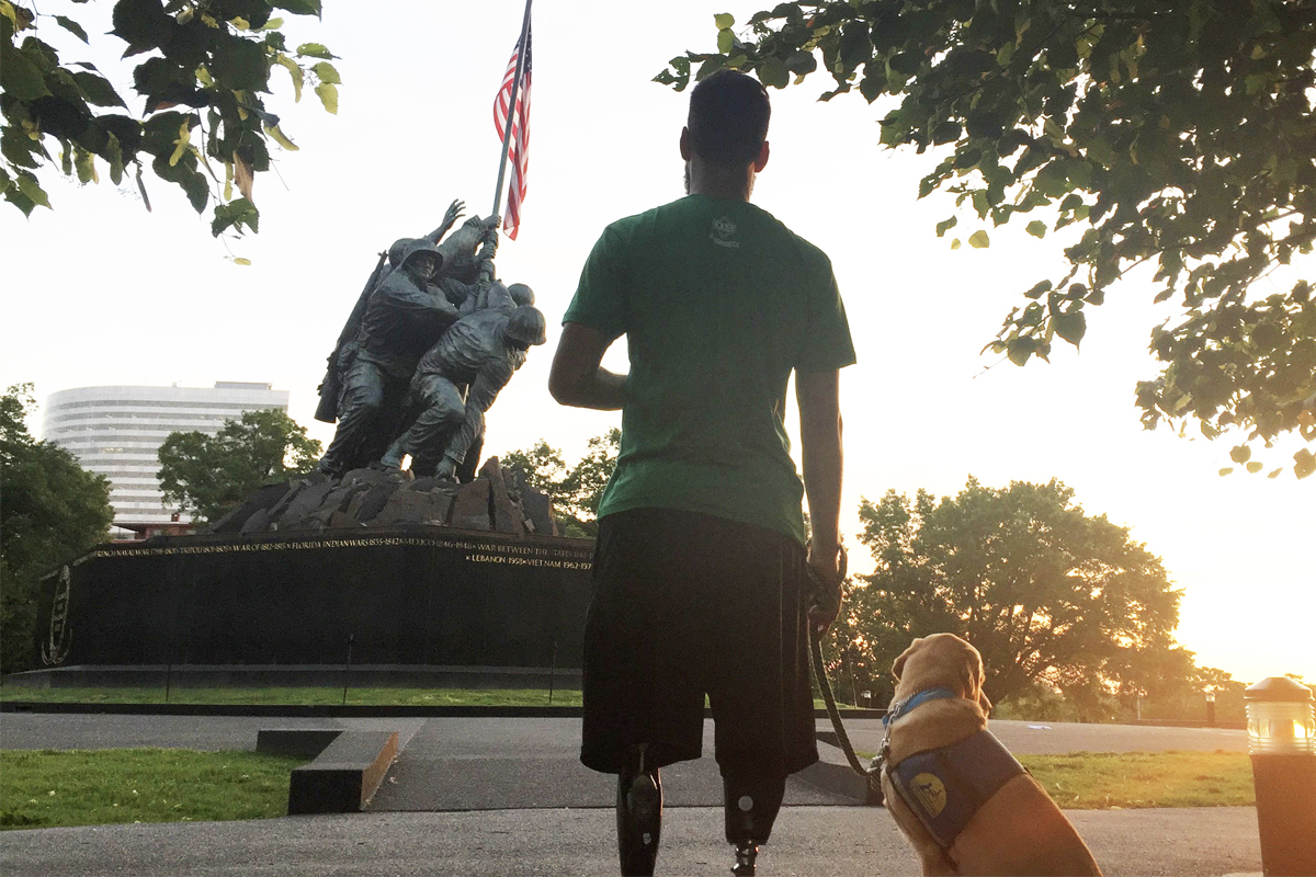 man standing with his back to the camera with a canine companions service dog