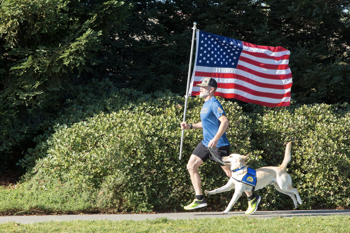 man running with Canine Companions service dog