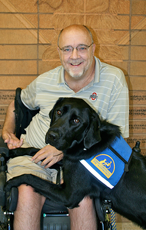 man sitting in wheelchair with black canine companions service dog