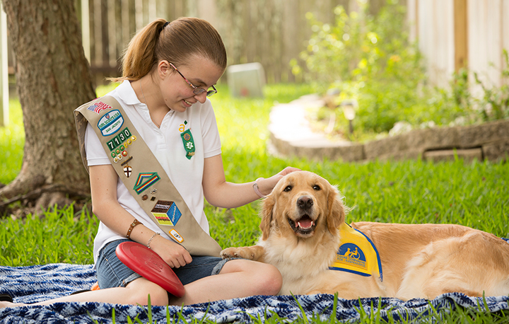 Girl scout sitting with Canine Companions golden retriever service dog