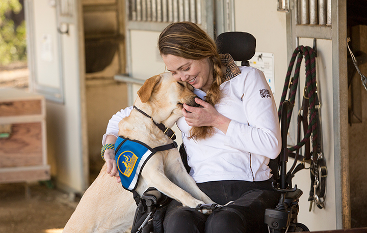 Woman in wheelchair cuddling with Canine Companions yellow dog