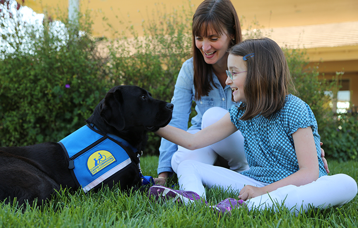 girl with mother and black canine companions service dog
