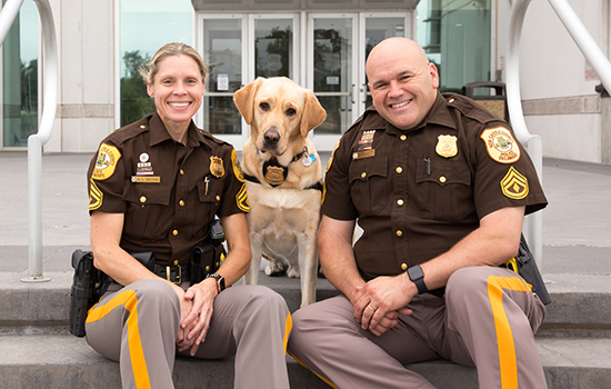 two poice officers sitting on steps next to Canine Companions assistance dog