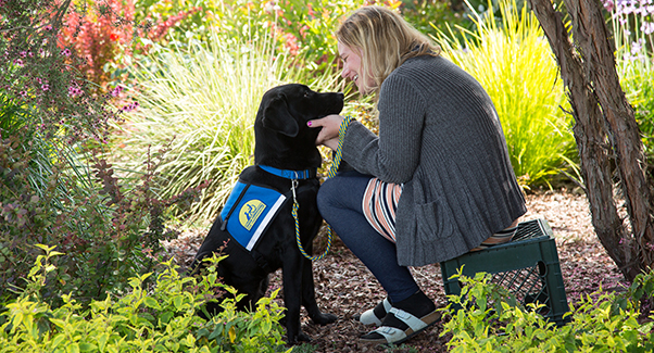 wooman sitting in flowers with black canine companions service dog