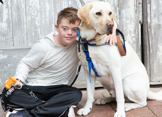 boy with his arm around Canine Companions service dog