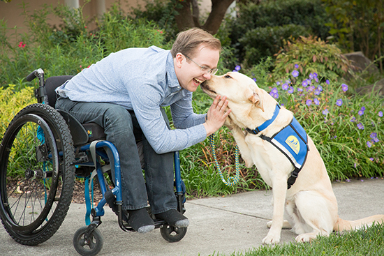 man sitting in wheelchair leaning forward kiss Canine Companions assistance dog