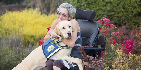Shakti sitting in wheelchair hugging Canine Companions Service Dog Ember