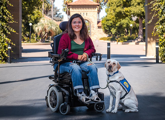 woman sitting in wheelchair with Canine Companions service dog by her side